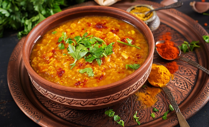 Traditional Indian soup lentils. Indian Dhal spicy curry in bowl, spices, herbs, rustic black wooden background. Authentic Indian dish.